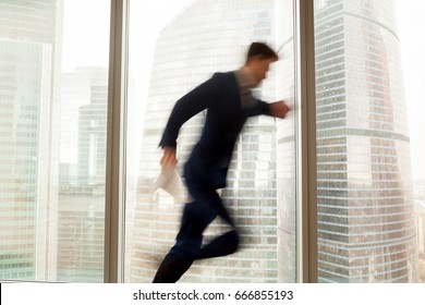 Busy businessman hurrying up to come at meeting on time in office building, blurred silhouette running in hurry along hallway, looking on wristwatch on the move, window city view at background