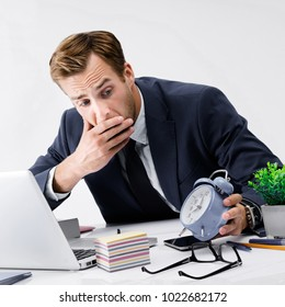 Busy businessman looking at alarm clock, in black suit working with laptop computer at office. Success in business, job and education concept shot.