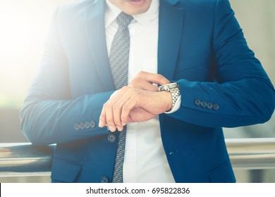 Busy businessman looking at wristwatch, In business time is important ,Portrait of businessman checking time.