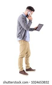 Busy businessman multitasking on the cellphone holding tablet computer. Full body length portrait isolated on white studio background.