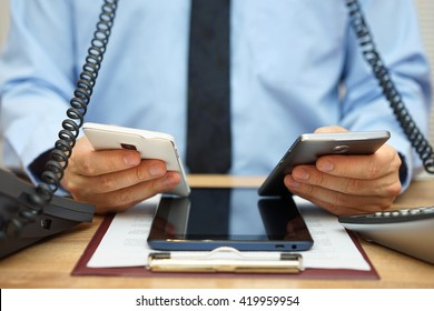 busy businessman in office at the desk using two mobile phones, two telephones and tablet computer