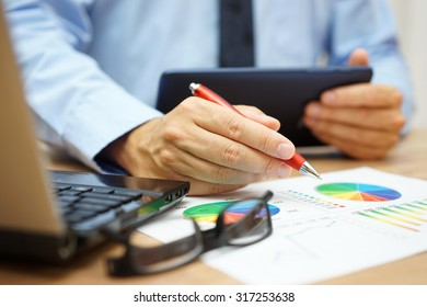 busy businessman overwhelmed with information  on tablet computer, laptop and documentation