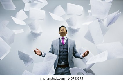 Busy businessman with pile of papers flying on air
