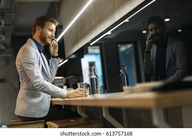Busy businessman talking on phone while sitting in a pub