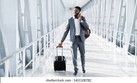 Busy Businessman Traveller Talking on Phone, Walking Inside Airport, Carrying Suitcase