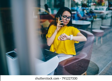 Busy businesswoman in eyewear looking at smartwatch while talking on cellular and agree on meeting sitting at laptop computer and working remotely.Manager managing time during phone conversation