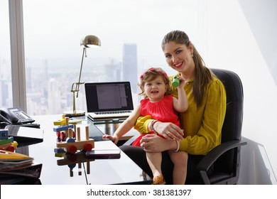 Busy businesswoman with little daughter in office. The executive mom spends time with her child and takes her at work
