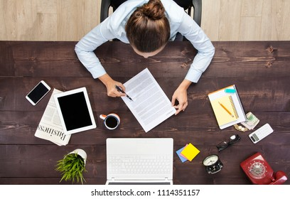 Busy businesswoman working at her office desk with documents and laptop, high angle view