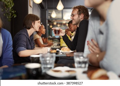 Busy cafe with a young couple smiling at each other