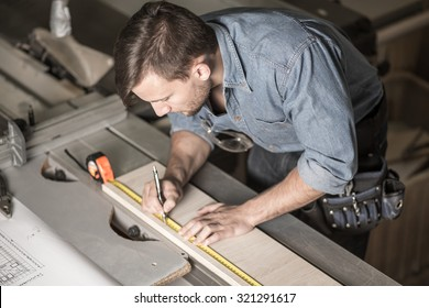 Busy carpenter using a measuring tape with precision