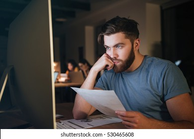 Busy caucasian bearded businessman working late at night with computer. Looking at computer while holding documents.