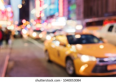 Busy city life blurred with taxi in foreground and street lights illuminating scene. Downtown in Times Square.