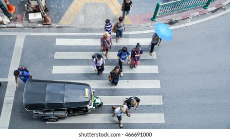 Busy city people crowd go pass pedestrian crossing on traffic road with the Tuktuk mini car. Bangkok, Thailand (Aerial photo, top view)