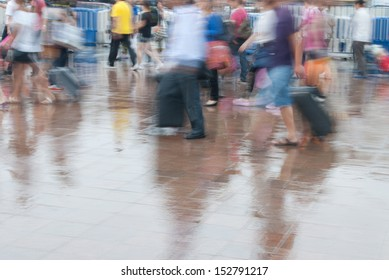 Busy city people walking after rain in motion blur