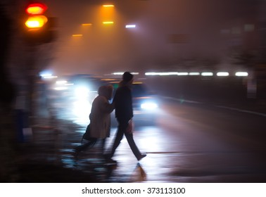 Busy city street people on zebra crossing at night. Dangerous situation. Intentional motion blur