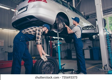 Busy colleagues professionals in special blue safety overalls uniform, head wear are torquing lugs nuts of wheel and rolling new rubber tyre, transportation is above. Safety, repair, assistance