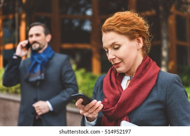 Busy colleagues using smartphones on street