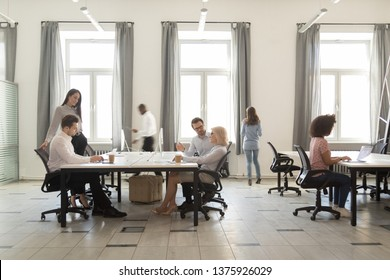 Busy company department members employees working together sitting at shared desks use computers walking in modern coworking space room interior daylight through windows, everyday office rush concept
