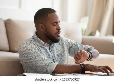 Busy concentrated african American male working on laptop at home look at hand watch checking time, focused biracial student typing studying on computer worried not miss appointment or deadline