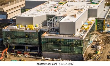Busy Construction site commercial building, large glass walls, warm tones