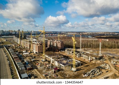 Busy Construction Site and Construction Equipment workers - aerial - Top View Photo. Crane and building construction