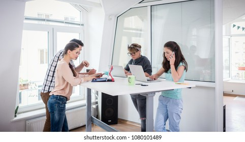 Busy co-workers using mobile technology connected to WI-FI network while sharing a desk in a modern work hub for freelancers and nomad entrepreneurs