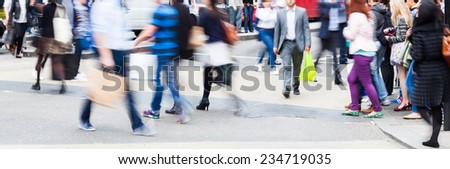 busy crowd of people in motion blur crossing a city street