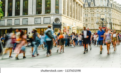 Busy crowds of anonymous motion blurred shoppers on London street