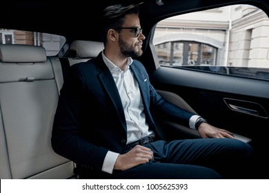 Busy day. Handsome young man in full suit looking through the window while sitting in the car
