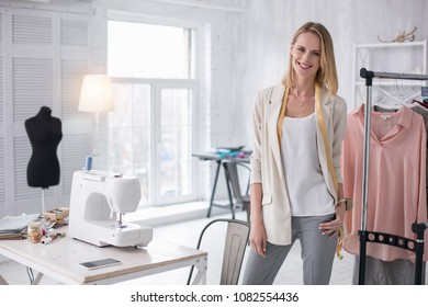 Busy day. Positive female tailor standing and looking at camera