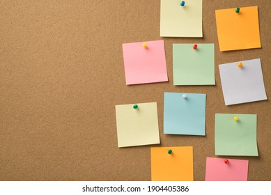 Busy day at work concept. Photo of lot of colorful notepaper attached with pins to the wooden board