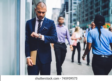 Busy executive manager in formal wear  hurrying for work walking on city street on urban settings, confident businessman looking at watch strolling on crowded avenue  trying to get to office in time