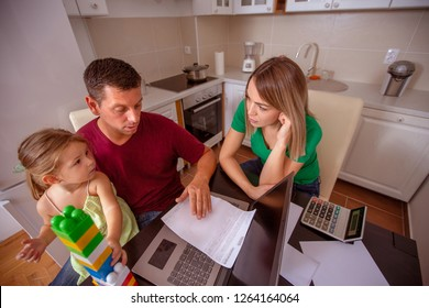 busy family - young couple with daughter planning home budget