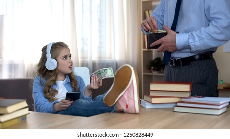 Busy father giving pocket money to little capricious daughter with headphones