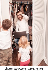 Busy father trying to find a quiet place in a wardrobe  to hide from children for a work at the laptop. Stay home concept. Quarantine. Freelancer.
