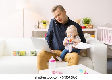 Busy father working with computer while looking after his baby girl