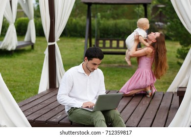 Busy father working on laptop at nature near his family