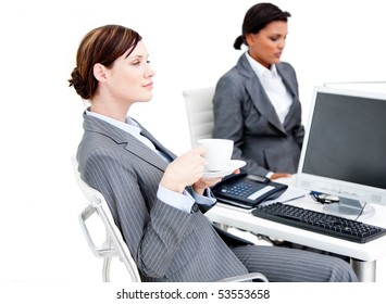 Busy female business partners drinking coffee while having a break in the office