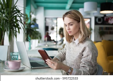 Busy female freelancer reading sms in cafe