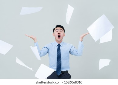Busy funny Asian business man overwhelmed by too much work and surrounded by flying paper