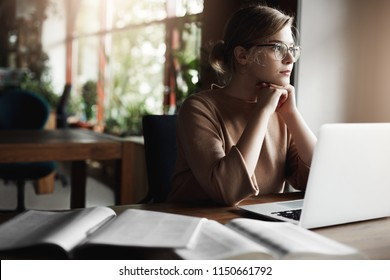 Busy and good-looking european female in glasses, leaning on hands, sitting in cafe while working remotely via laptop. Woman got carried away with thoughts in middle of studying, gazing through window