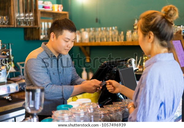 Busy handsome coffee shop employee taking credit card while working with customer. Serious confident cashier standing at digital cash machine. Staff concept