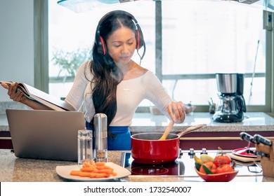 Die bedienerfreundlichen Mitarbeiter des Betreibers arbeiten in Videokonferenzen mit Kopfhörer und Mikrofon. ein Laptop in der Küche während des Kochens im Strom roten Topf. Arbeiten von zu Hause Konzept.