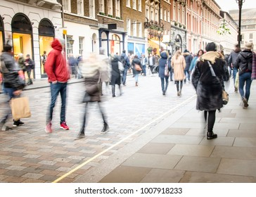 A busy high street with anonymous crowds of shoppers with shopping bags