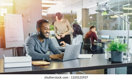 Busy International Office, African-American Man Working at His Desk on a Laptop, in the Background Businesswomen Discuss Relevant Data. Stylish Office with Talented Young People.