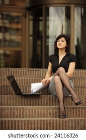 busy lady with sexy legs outdoors with laptop on steps outside a office building