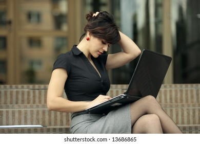 Busy lady with sexy legs. Young attractive business lady working at the laptop outdoors in front of an office building and playing with her hair in Cluj-Napoca city