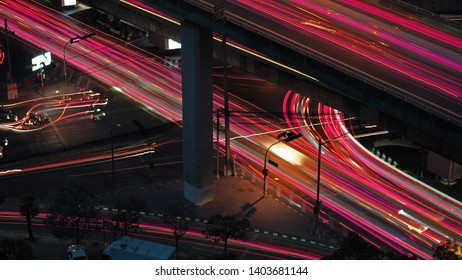 Busy main road intersection in city arear with car and motorcycle blured light trails.