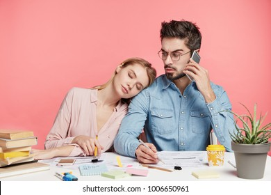 Busy male worker has phone conversation, writes something in documents, looks at his colleague who sleeps at shoulder, fatigue and exhausted, isolated over pink background. Togetherness concept