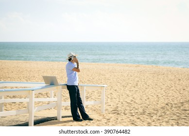 Busy male working on the laptop and talking on mobile. Man in hat speaking on smartphone over blue sky and ocean beach background